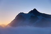"Mount Shuksan, 9,127-foot (2,782-meter) peak located in the North Cascades National Park in Washington, stands tall over a fog bank. Shuksan is derived from a Skagit Indian word meaning ""rocky and precipitous."""