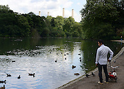 © Licensed to London News Pictures. 21/07/2012. London, UK A man looks at a lake with Battersea Power Station in the background. People enjoy the warm weather in Battersea Park today 21st July 2012. Photo credit : Stephen Simpson/LNP
