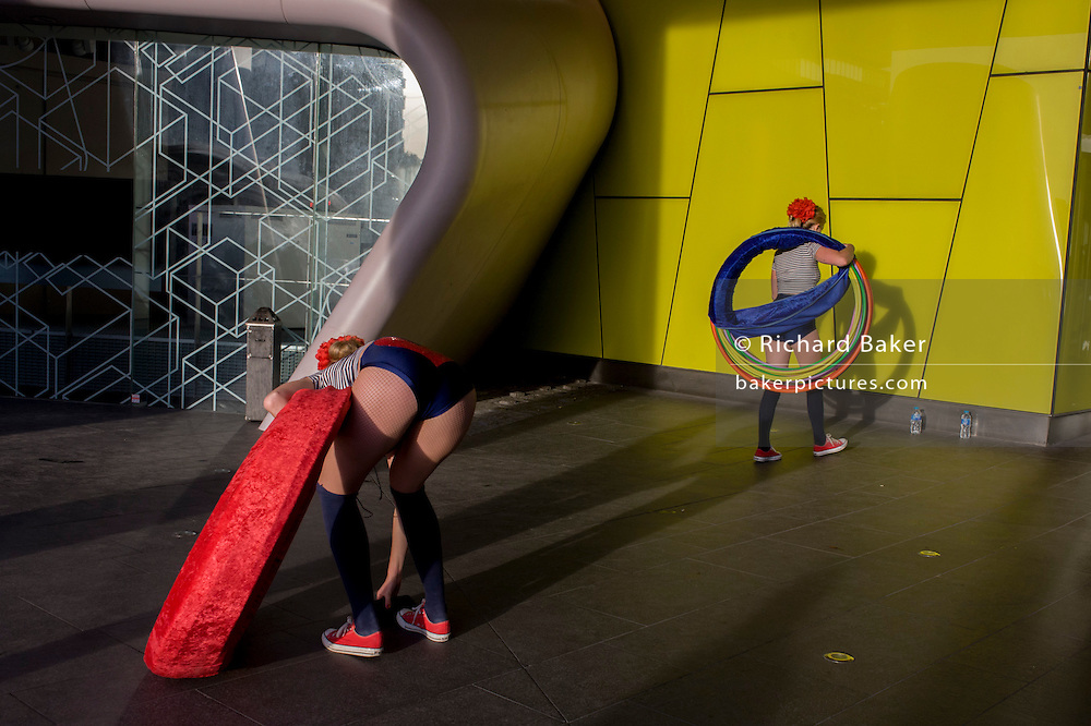 As part of London's Bankside 'Merge 2015' are street performers taking part in the arts festival, located at various spots on the southern side of the Thames and supported by tate Modern and Better Bankside. Here hula-hoop girls entertain commuters outside offices in Southwark as they interact with their surroundings and those rushing home on a Thursday evening.