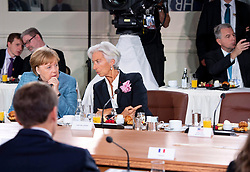 IMF Managing Director Christine Lagarde, centre, points towards the empty seat of U.S. President Donald Trump next to her, as she speaks with Chancellor of Germany Angela Merkel, left, during the G7 leaders summit in La Malbaie, Que., on Saturday, June 9, 2018. Photo by Justin Tang/CP/ABACAPRESS.COM