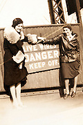 two female friends standing and smiling by a danger sign