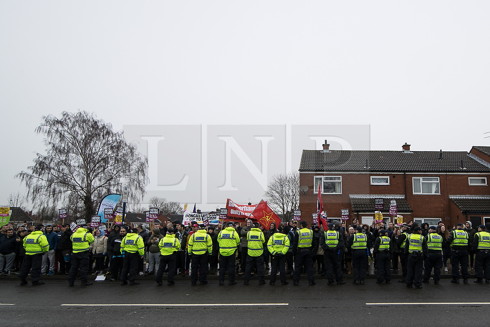 © Licensed to London News Pictures . 20/01/2018. Doncaster, UK. An anti-fascist counter protest is kept apart from the EDL demonstration by a wall of police . Far-right street protest movement , the English Defence League ( EDL ) , hold a demonstration , opposed by anti-fascists , including Unite Against Fascism ( UAF ) in the Hexthorpe area of Doncaster . EDL supporters chanted anti-Roma slogans as they marched through the town . Photo credit: Joel Goodman/LNP