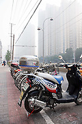 Motor scooters parked in formation along a street adjacent to high rise accommodation blocks in downtown Shanghai.