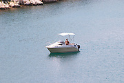 A small pleasure boat with a sun shade floating in the sea in a bay. A man sitting in the boat. Dubrovnik region. Dalmatian Coast, Croatia, Europe.