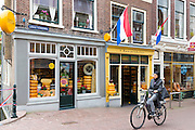 Woman wearing muslim veil cycles past cheese shop 't Kaaswinkeltje in Lange Tiendeweg in Gouda, Holland, The Netherlands