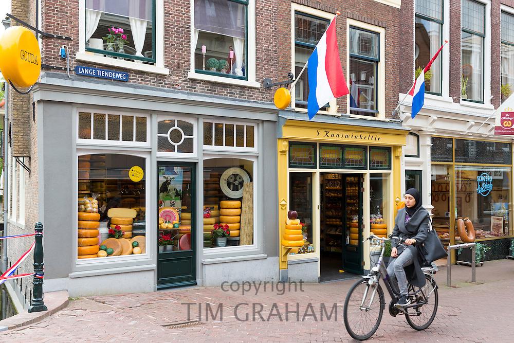 Woman wearing muslim veil cycles past cheese shop 't Kaaswinkeltje in Lange Tiendeweg in Gouda, Holland, The Netherlands