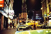 Neon lights at night city centre of Amsterdam, Netherlands 1970s - 1980s, yellow tramcar Munttoren tower