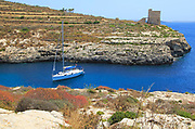 Yacht and watchtower at entrance to Mgarr ix-Xini coastal inlet, island of Gozo, Malta