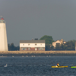 Sea kayaking with fishing gear in the mouth of the Connecticut River between Old Saybrook and Old Lyme, Connecticut.  Old Saybrook Lighthouse.  Long Island Sound.