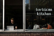 A young man using an Apple Mac laptop computer at the Barbican Kitchen at the Barbican Centre on the 12th September in London in the United Kingdom.