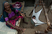 Rabari woman with baby in swinging bed. She is wearing her everyday dress and jewellery. Rabari is a term used for tribal cattle herders. Jewellery is their wealth and they never take it off. They have very ornate earrings and large silver bangles and plastic upper arm bracelets.  These used to be made of ivory - some of the older woman still have ivory & silver overlayed bangles. Many of the Rabari woman have ornate tatoos on their faces, necks, chests and arms. Designs such as peacocks and other religious symbols are usually done during festivals when the tatoo artists come to town. The Rabari men too wear heavy ornate earrings.<br /> Gujarat. Rann of Kutch. SW INDIA