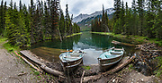 Rowboats at Beaver Lake, Jasper National Park, Canadian Rockies, Alberta, Canada. With 1km of rerouting discouraging our bikes on flooded Jacques Lake Trail on 01 July 2019, we instead hiked on foot for 6 miles to scenic Beaver Lake, then nearly to Summit Lake before turned back by rain, in Jasper National Park, Canadian Rockies, Alberta, Canada. Jasper is the largest national park in the Canadian Rocky Mountain Parks World Heritage Site, honored by UNESCO in 1984. This image was stitched from multiple overlapping photos.