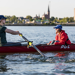 Two women (a rower and coxswain) from the Portland Community Rowing Association row in Back Cove in Portland, Maine.