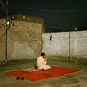 A man does his evening prayer in the city center. In the city of Jacobabad.