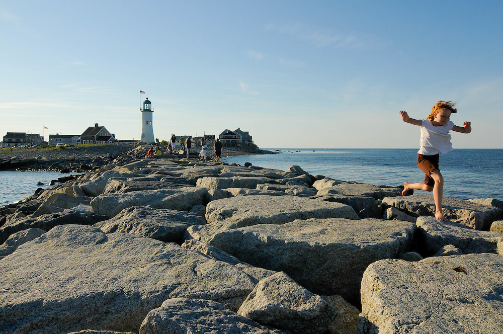 A young girls runs the jetty at Scituate Light on a late summer afternoon.