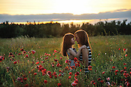 Outdoor portrait of a mother and daughter in a red poppy field during sunset by Kristina Cilia Photography