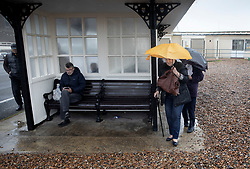 © Licensed to London News Pictures. 14/08/2019. West Sussex, UK. A group of day-trippers (R) from Bermondsey, south London brave the wind and rain on the seafront at Worthing on the south coast. Parts of the United Kingdom are exeriencing heavy unseasonable rain today. Photo credit: Peter Macdiarmid/LNP