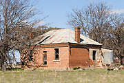 Dilapidated rundown old brick farm house in paddock near Molong, New South Wales, Australia <br />