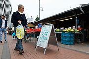 A man holding a shopping bag passes a Covid-19 social distancing sign as he browses fresh fruit and vegetables at the outdoor market on 4th September, 2021 in Leeds, United Kingdom. A combination of Brexit and Covid-19 is reportedly exacerbating an already severe staff shortage in the British food industry, with a lack of fruit and vegetable pickers that could see a hike in food prices across the country.