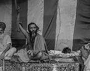 A Holy man (Sadhu)  sits in his tent at Kumbh Mela in Prayagraj, India. As an ascetic practice, he has held his arm in this position for 10 years.