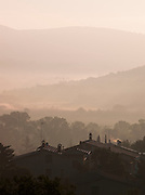 A misty morning sunrise over the sleepy village of Solomeo in the hills of Umbria, Italy