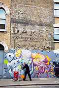 Elderly woman pushes her shopping cart past a wall which transcends two centuries. In this street in Camberwell in South London, a wall which shows the historic remains of an old advertising sign is contrasted by some modern graffiti street art. This contrast of old and new, young and old is a strong illustration of how times have changed in community and society.