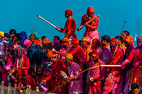 Men with squirters spraying the crowd below with different color liquids as large crowds celebrate Lathma Holi in the village of Nandgaon, near Mathura, during Holi (festival of colors), Uttar Pradesh, India.