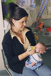 Mother on Neonatal unit feeding premature oxygen dependent baby; which was born at 28 weeks and is now 17 weeks old; using bottle and tube,