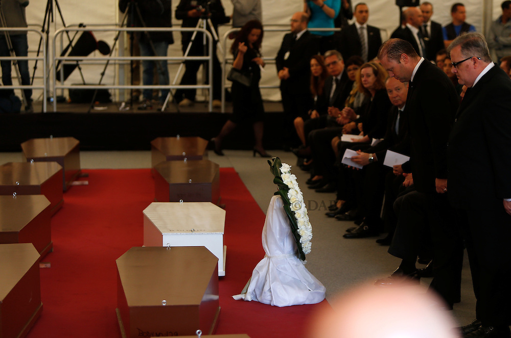 Malta's Prime Minister Joseph Muscat (2nd R) pays his respects in front of the 24 coffins with the bodies of migrants during an inter-faith burial service at Mater Dei Hospital in Tal-Qroqq, outside Valletta, April 23, 2015. European Union leaders who decided last year to halt the rescue of migrants trying to cross the Mediterranean will reverse their decision on Thursday at a summit hastily convened after nearly 2,000 people died at sea.  Public outrage over the deaths peaked this week after up to 900 migrants died last Sunday when their boat sank on its way to Europe from Libya.<br /> REUTERS/Darrin Zammit Lupi MALTA OUT. NO COMMERCIAL OR EDITORIAL SALES IN MALTA