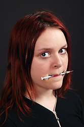 Teenage girl holding a syringe in her mouth,