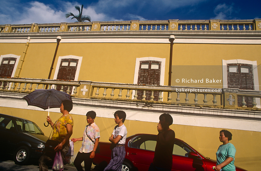 Local Mecanese (Macau-born Chinese) walk past heritage architecture from the island's colonial Portuguese era, on 10th August 1994, in Macau, China. The Macau Special Administrative Region is one of the two special administrative regions of the People's Republic of China (PRC), along with Hong Kong. Administered by Portugal until 1999, it was the oldest European colony in China, dating back to the 16th century. The administrative power over Macau was transferred to the People's Republic of China (PRC) in 1999, 2 years after Hong Kong's own handover.