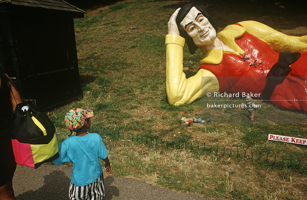 Young boy looks at reclining giant figure resembling Gulliver's Travels in Lilliput on Southend seafront.