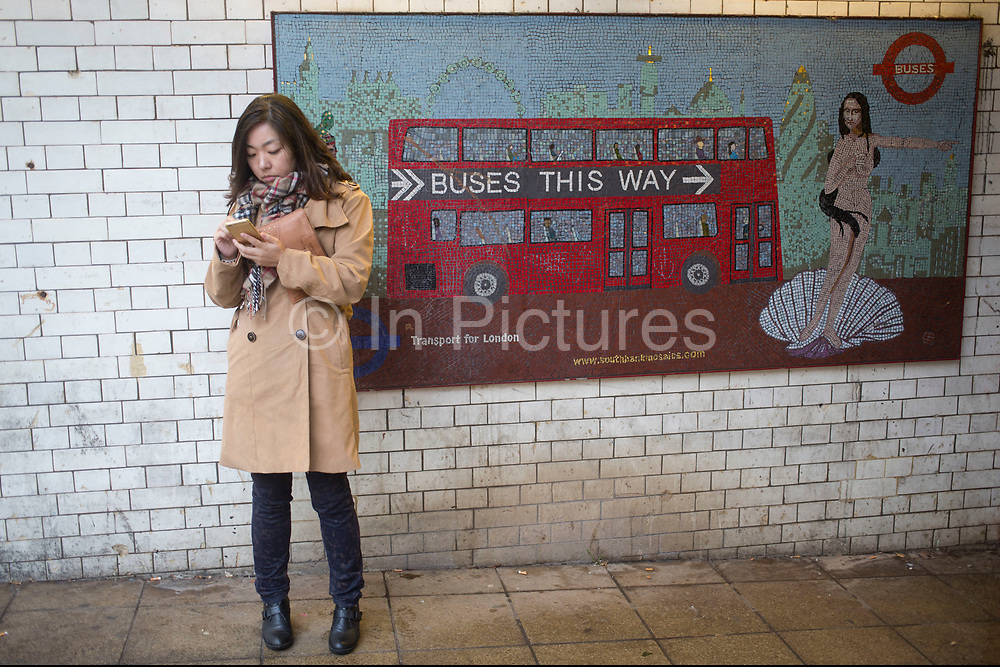 Asian woman checking her smartphone next to to a mosaic which seems to duplicate her in the form of a two dimensional nude of a Mona Lisa, who is pointing the direction to find public transport buses. London, UK.
