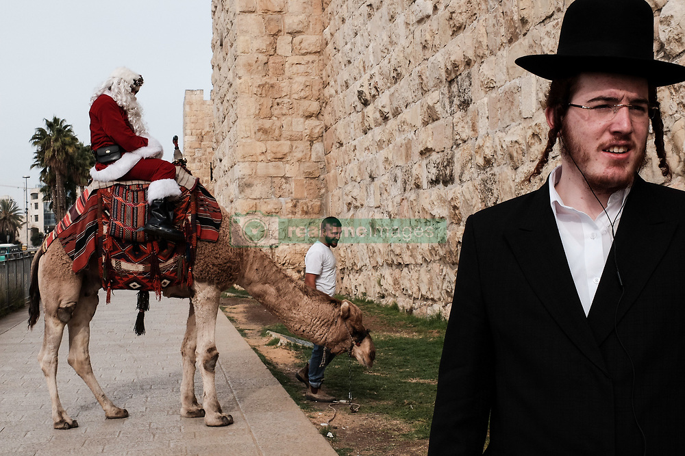 December 21, 2017 - Jerusalem, Israel - An ultra Orthodox religious Jewish man passes Santa Claus, or 'Baba Noel' as he is called in Arabic, as he rides a camel substitute for rain deer near Jerusalem's Old City Jaffa Gate. The Jerusalem Municipality and the Jewish National Fund distributed specially grown Arizona Cypress Christmas trees to the Christian population at the Jaffa Gate. (Credit Image: © Nir Alon via ZUMA Wire)