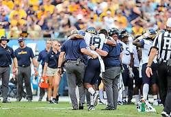 Sep 1, 2018; Charlotte, NC, USA; West Virginia Mountaineers linebacker Charlie Benton (18) is helped off the field after an injury against the Tennessee Volunteers during the second quarter at Bank of America Stadium. Mandatory Credit: Ben Queen-USA TODAY Sports