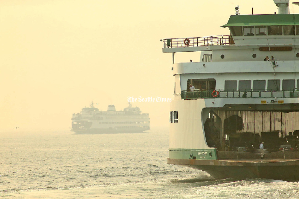 Smoky haze envelopes the Bremerton ferry Walla Walla, left. The boat was arriving in Seattle as the ferry Wenatchee, right, departed for Bainbridge Island. (Greg Gilbert / The Seattle Times, 2018)