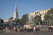Water fountain, statue, people, Trafalgar Square, London, England with Saint Martin in the Fields church