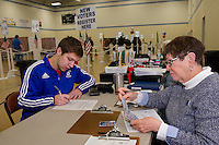 """Christian Karagianis fills out paperwork as a """"first time"""" voter with Mary Vilaume at the Gilford Community Center during the NH Primary on Tuesday morning.  (Karen Bobotas/for the Laconia Daily Sun)"""