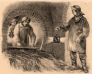 Flushing a London sewer.  The men are dressed in oilskins and hold bull's eye lanterns to give them enough light to carry out their work.  Engraving from 'London Labour and the London Poor' by Henry Mayhew (London, 1861).