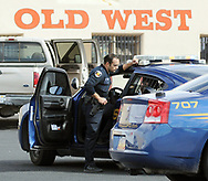Las Cruces police officer Frank Gomez talks to a suspect in the back of his police unit on Wednesday, Feb. 11, 2015, at Bowlin's Old West Trading Post at exit 127, where a high-risk pursuit ended.