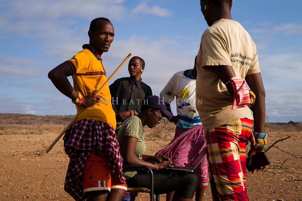 Grevy's Zebra Trust staff check camera trap data in the field with Samburu elders.