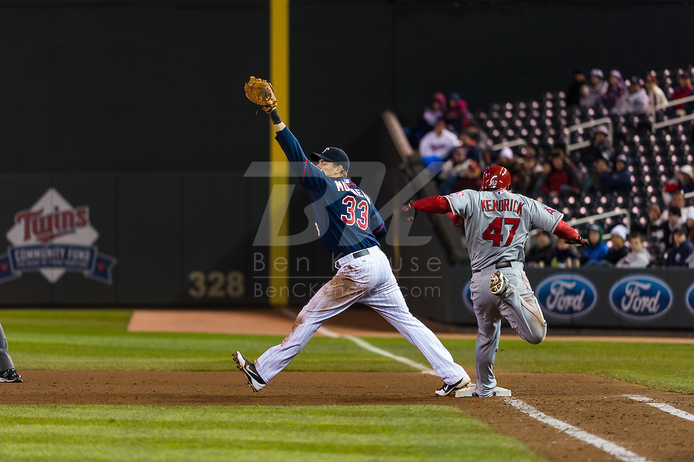 Justin Morneau #33 of the Minnesota Twins reaches for a throw at 1st base ahead of Howie Kendrick #47 of the Los Angeles Angels on April 16, 2013 at Target Field in Minneapolis, Minnesota.  The Twins defeated the Angels 8 to 6.  Photo: Ben Krause