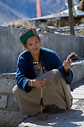 An older woman in traditional Kinnauri clothing spinning yarn on 20th October 2009, Himachal Pradesh, India. The region of Spiti and Kinnaur is a remote and tribal area of the Indian Himalayas near the Tibetan border.