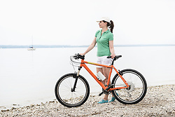 Mature woman with electric bicycle at lakeshore, Bavaria, Germany