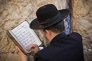 A man reads a religious text at the Western Wall, in the Old City, Jerusalem, Israel.