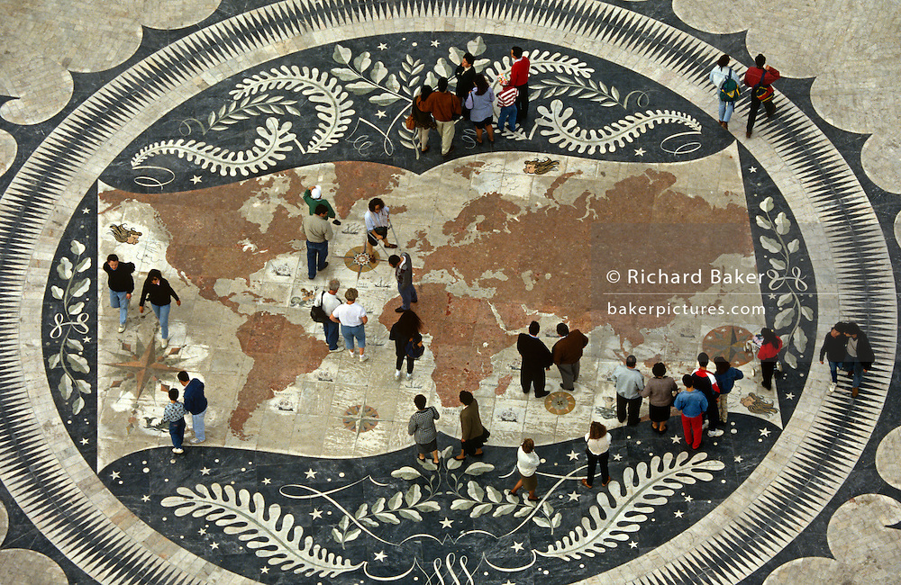 Portuguese pedesrtians walk over a world map on the pavement beneath the Monument of Discoveries, Lisbon.