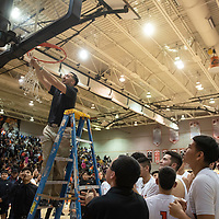 Gallup Bengals head coach Joshua Dunlap cuts down the net following Gallup Bengals 1-4A district championship win  against the Kirtland Central Broncos Friday night at Gallup High School in Gallup.