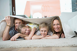 Happy family with two kids at home, lying on floor under blanket