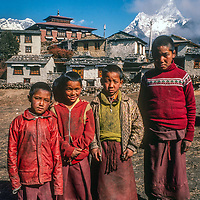 Young Tibetan Buddhist monks pose at Tengboche Monastery in the Khumbu region of Nepal. This picture was shot in 1986 before the monastery was destroyed in an 1989 electrical fire and subsequently rebuilt in a more modern form.