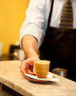 Spella Caffe, a tiny, Italian style coffee shop in downtown Portland, Oregon specializes in traditional espresso and espresso drinks using their own roasted coffee beans.  Pictured here is the owner Andrea Spella making the shakeratto - a shot of espresso and a spoonful of sugar blended on ice in a cocktail shaker and served in a glass.